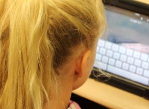 enfant qui tape sur un écran de tablette
