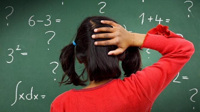 Image d'une petite fille devant des calculs qui semble perdue