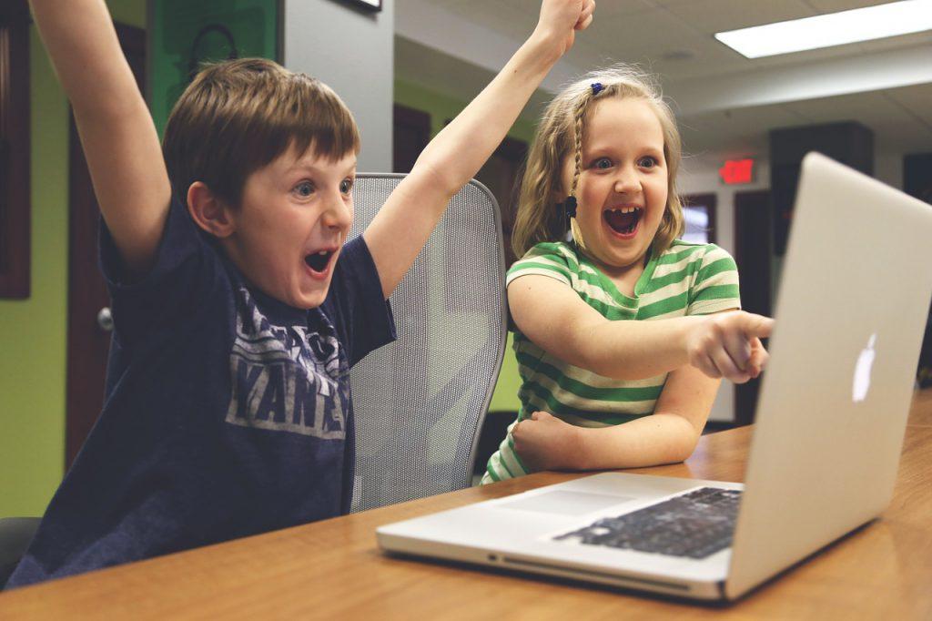 Deux enfants qui crient de joie devant un ordinateur