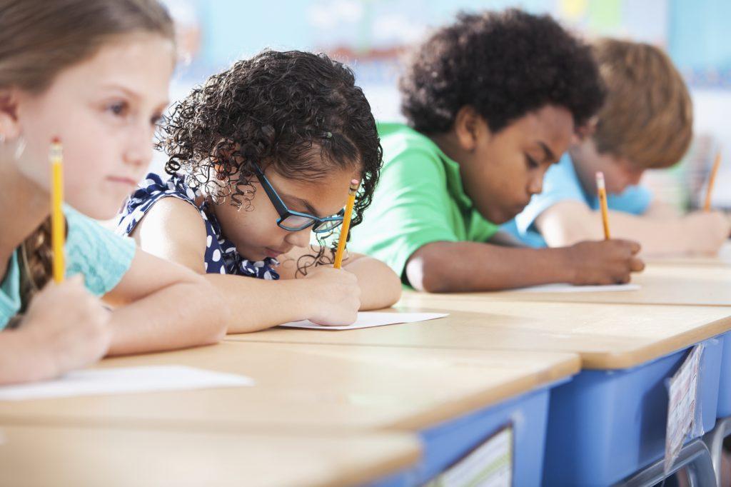 des enfants très concentrés en train d'écrire un crayon à la main