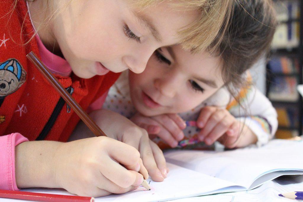 Deux enfants concentrés en train d'écrire